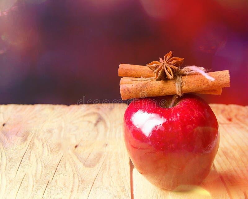 红色光滑的苹果肉桂条栓与麻线在木桌上的茴香星在闪烁的诗歌选bokeh光 r 免版税图库摄影