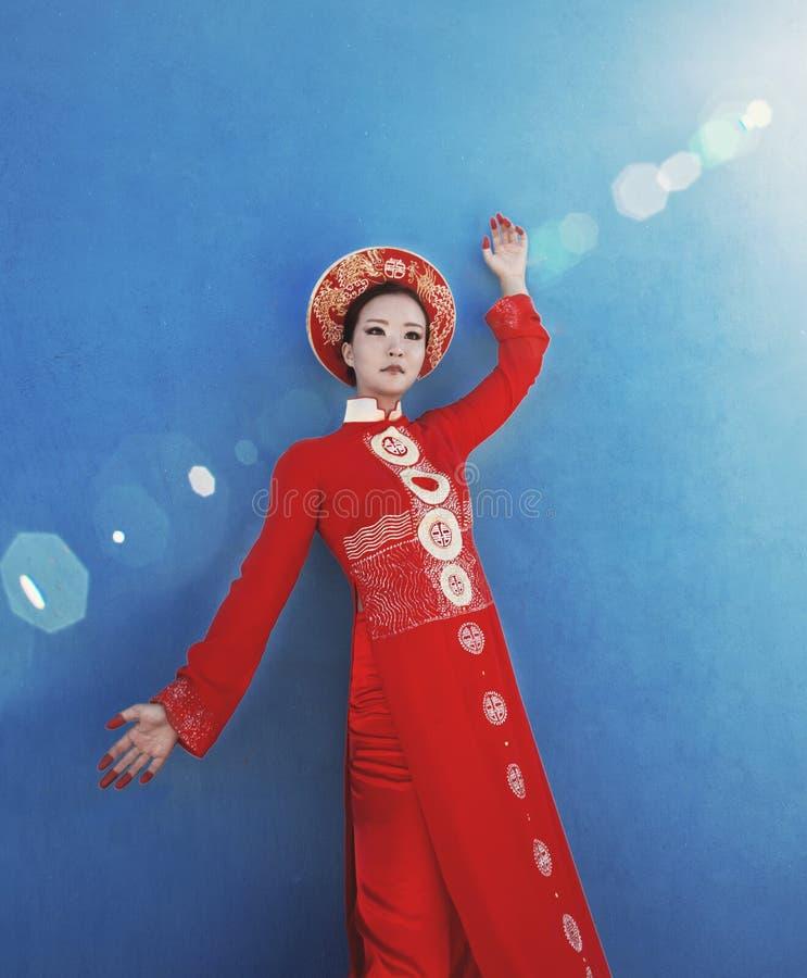 红色全国民族服装的秀丽年轻越南妇女 免版税库存照片