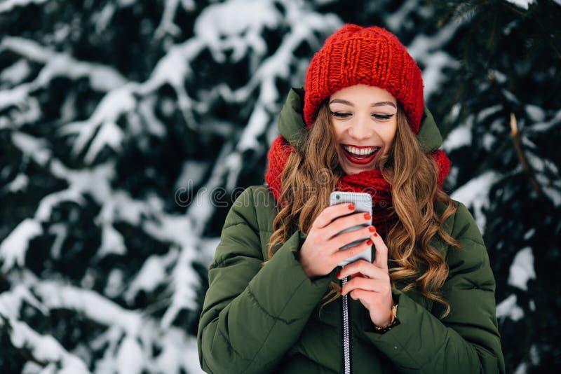 红色冬天帽子和围巾的女孩使用智能手机和微笑 免版税库存照片