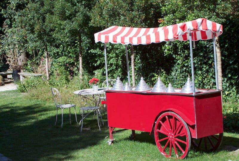 红色冰淇凌推车在庭院里 库存图片