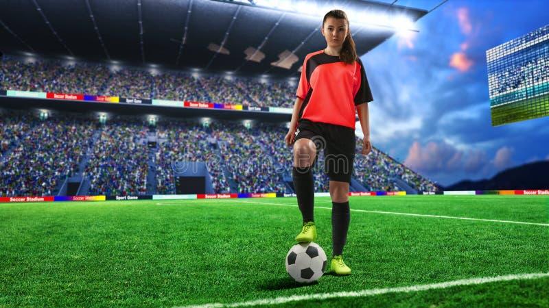 红色制服的女性足球运动员在足球场 免版税库存图片