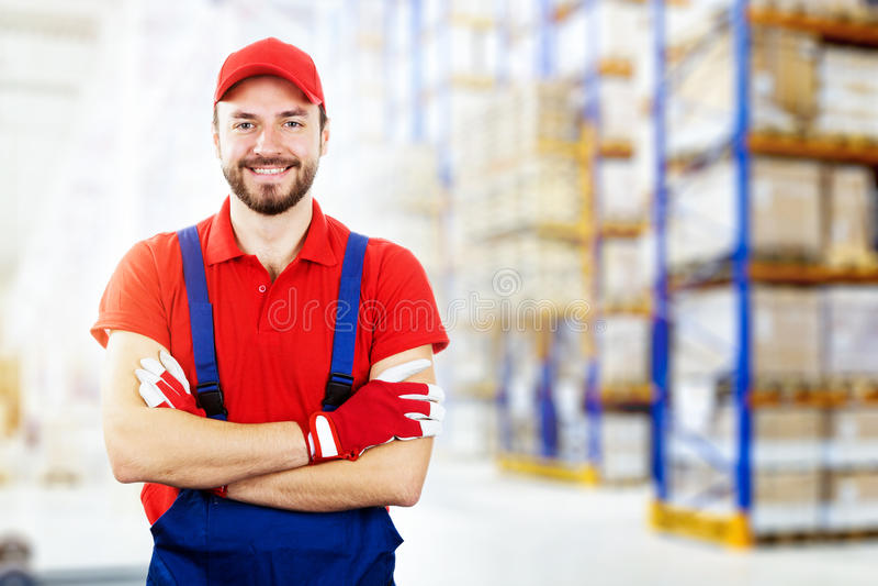 红色制服的微笑的年轻仓库工作者 免版税库存图片