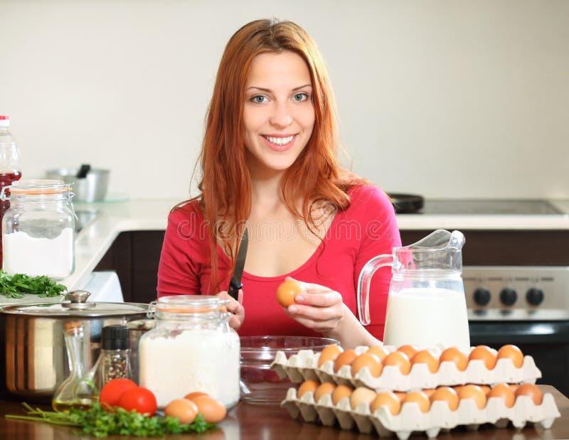 红色制造的面团的妇女在国内厨房里 免版税库存图片