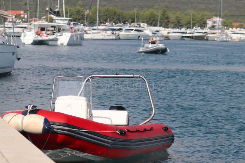 红色可膨胀的汽船在小游艇船坞的背景中被停泊到码头有游艇的 协助的试验船  免版税库存照片