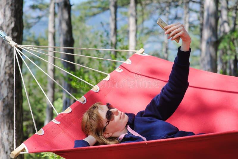 红色吊床的,森林女孩 库存图片