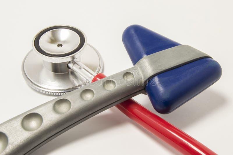 红色听诊器和神经学反射锤子有横向蓝色三角顶头谎言的在白色背景在医生工作场所 EQ 库存照片