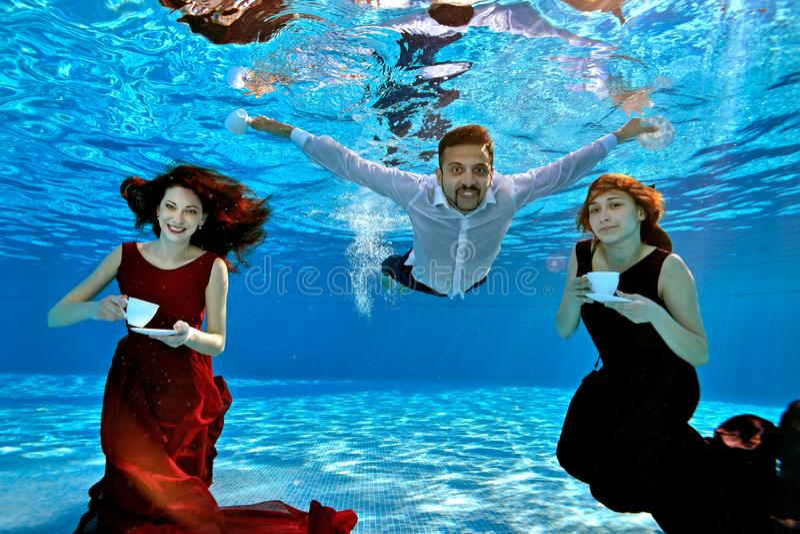 红色和伯根地礼服的两个美丽的女孩和白色衬衣游泳和戏剧的一个人水下在水池 他们举行白色c 免版税库存照片