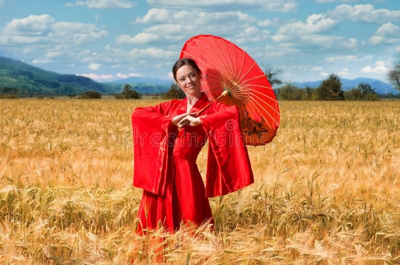 红色和服的妇女在麦田 免版税库存图片