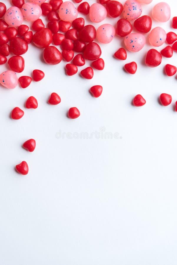 红色和桃红色华伦泰` s天桂香心脏和豆形软糖有白色背景 免版税库存图片