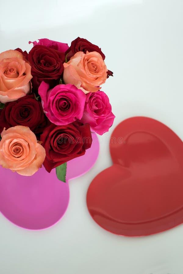 红色和桃红色玫瑰安排了在桃红色心形的板材顶部 库存图片