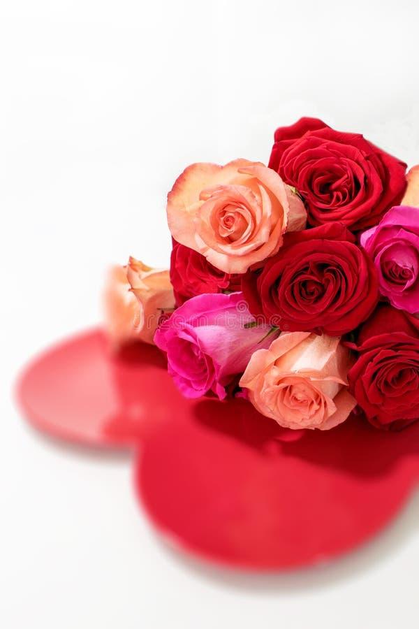 红色和桃红色玫瑰花束在红色心脏的 免版税图库摄影