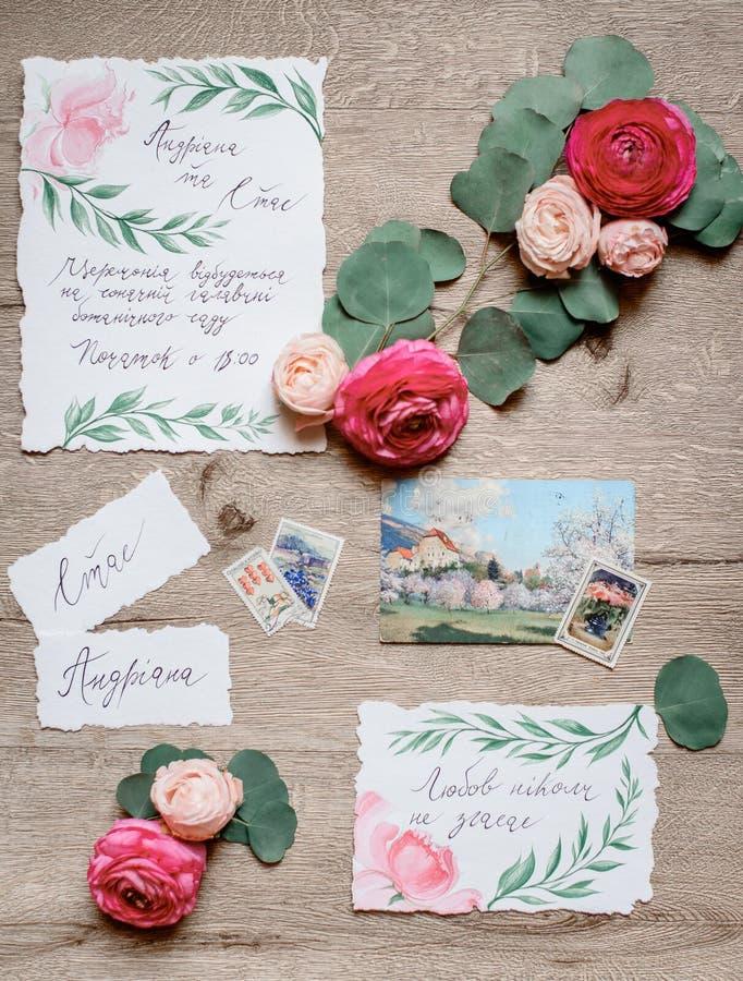 红色和桃红色花在与喜帖的桌上说谎 免版税库存照片