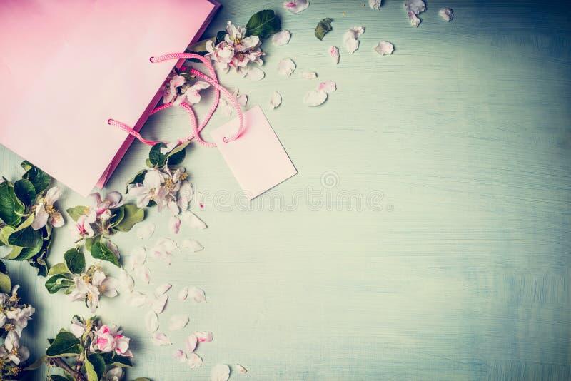 红色和桃红色购物袋与夏天或春天花和叶子在一个轻的薄荷的背景、顶视图、框架春天或者夏天s 免版税图库摄影