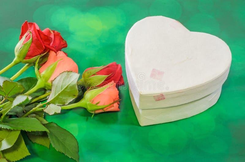 红色和橙色玫瑰开花与心脏形状箱子,情人节,绿灯bokeh背景,关闭 免版税图库摄影