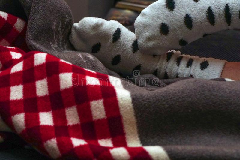 红色和白色毯子和脚与在家使接近变冷看法的白色被加点的袜子 库存照片