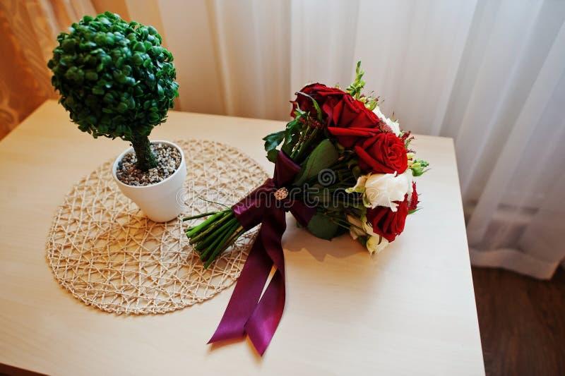 红色和白色玫瑰和丝带婚礼花束在桌上 免版税库存照片