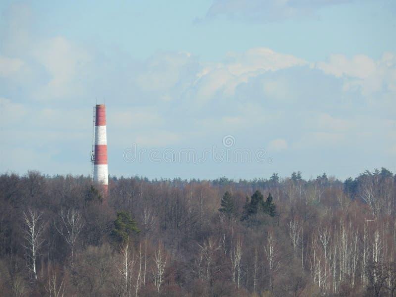 红色和白色老在天空蔚蓝背景的砖工业管子 产业概念的老图象 生态,工业更新 库存图片