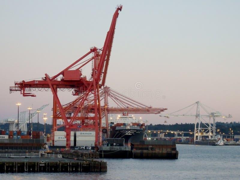 红色和白色起重机卸载了货物在黄昏 图库摄影