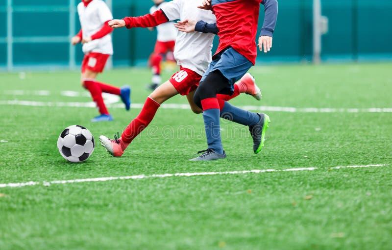 红色和白色运动服的男孩踢在绿草领域的足球 青年橄榄球赛 儿童体育竞赛 免版税库存照片
