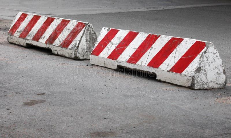 红色和白色镶边混凝土路障碍 免版税库存照片