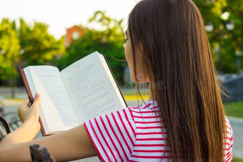 红色和白色T恤杉的可爱的妇女享用在长凳的一本书在公园在夏日 一少妇readi的后面看法 免版税库存照片