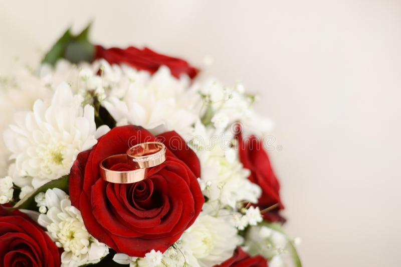 红色和白花结婚戒指和花束  与拷贝空间的轻的背景 库存图片