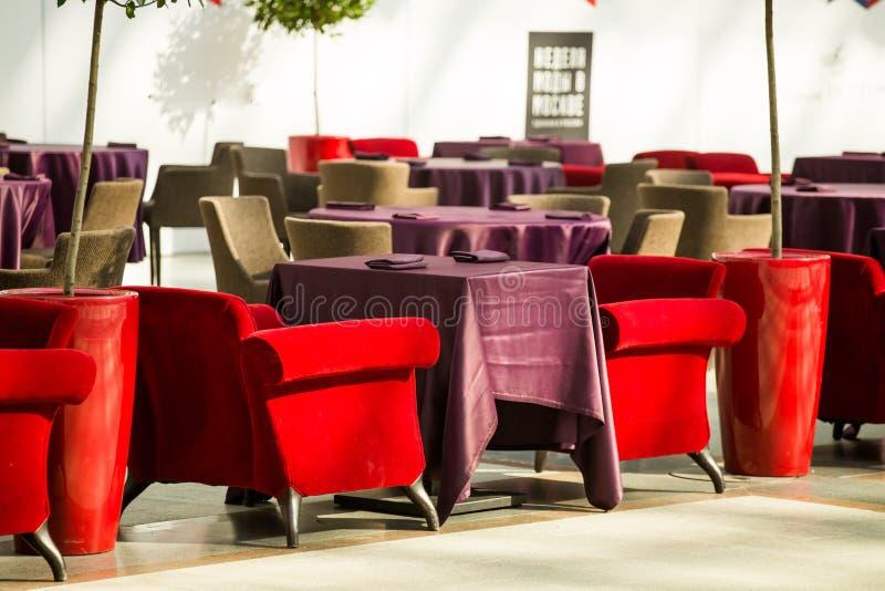 红色和米黄扶手椅子是在餐馆桌旁边,用长的伯根地桌布盖 免版税图库摄影