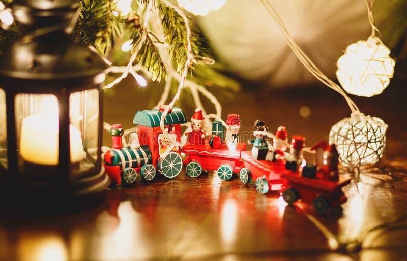 红色和绿色火车立场在光的杉树下在地板上的黑烛台旁边 圣诞节新年度 免版税库存照片
