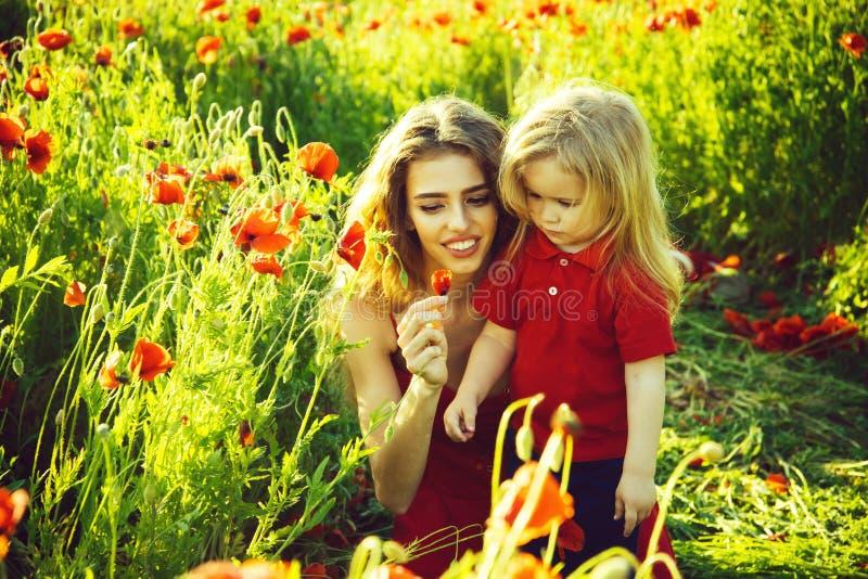 红色和绿色,微笑的母亲和孩子鸦片领域的 免版税库存图片