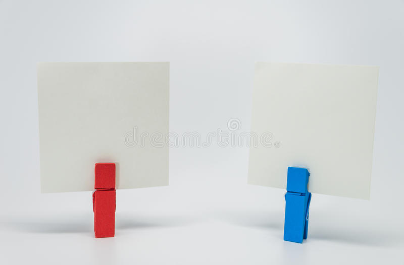 红色和蓝色木夹子夹紧的备忘录纸张有白色背景和选择聚焦 库存图片