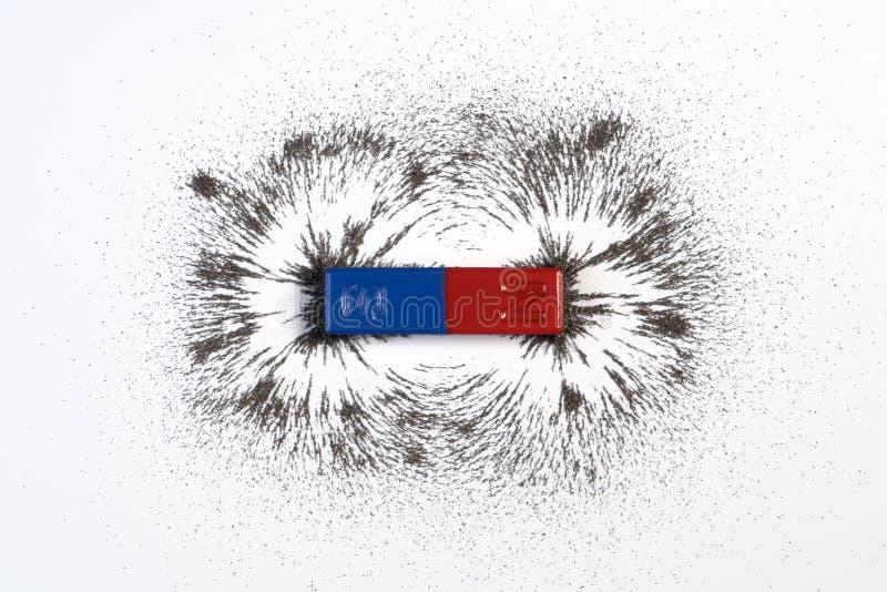红色和蓝色磁铁棒或物理磁性与铁粉末mag 免版税库存图片