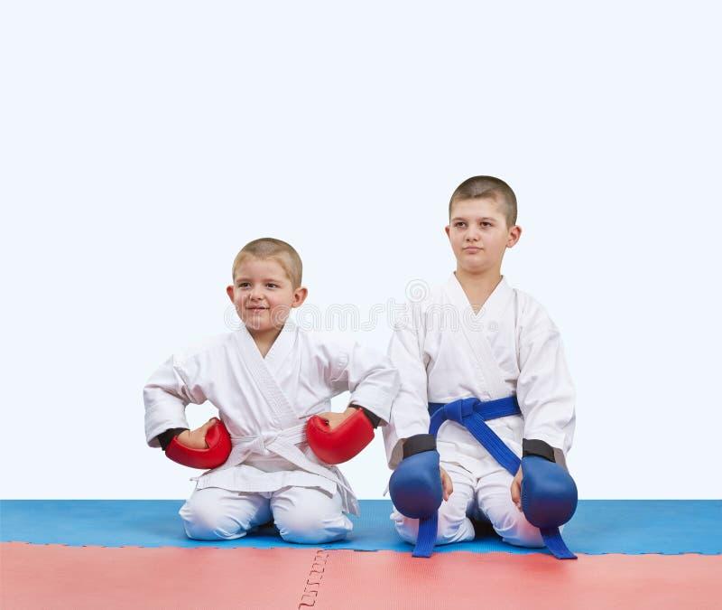 红色和蓝色覆盖物的两位男孩运动员坐席子 免版税库存图片