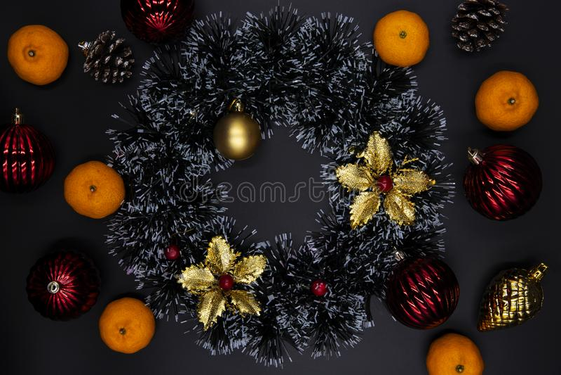红色和金子圣诞树装饰和蜜桔在黑背景 寒假季节顶视图构成 免版税库存图片