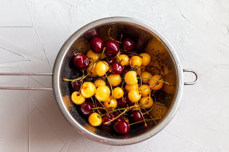 红色和黄色樱桃莓果和桃子被混合在一块板材,夏天新鲜的健康食品,与空间的图片文本的 库存图片