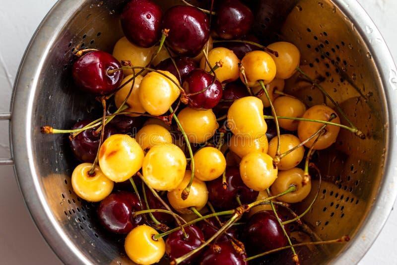红色和黄色樱桃莓果和桃子被混合在一块板材,夏天新鲜的健康食品,与空间的图片文本的 免版税库存照片