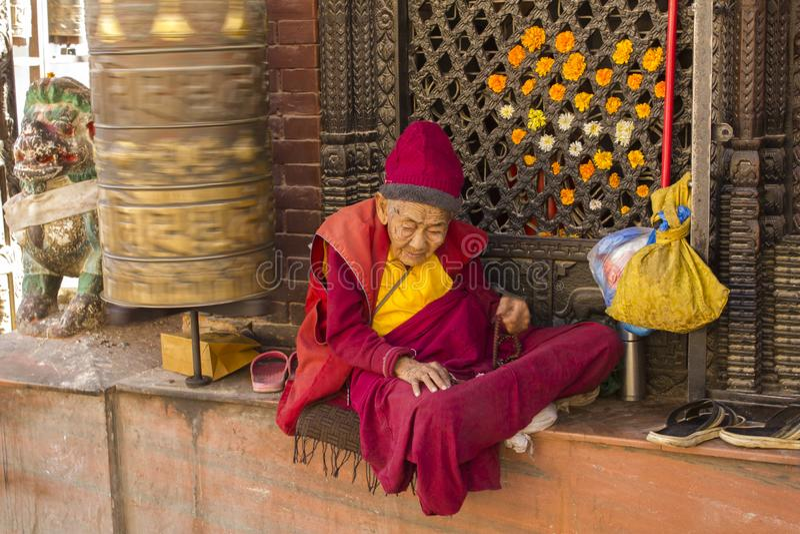 红色和黄色衣裳的一个非常老西藏和尚在一个转动的祷告鼓附近坐 免版税库存照片