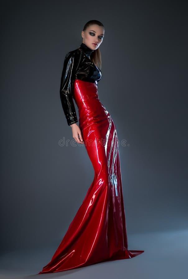 红色和黑乳汁礼服的美丽的深色的妇女 库存图片