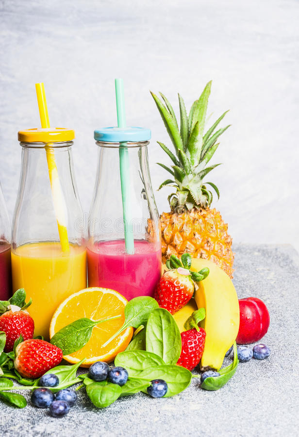 红色和黄色圆滑的人在有果子成份的瓶喝在轻的背景 健康生活方式 库存图片