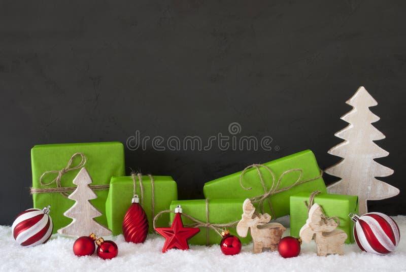 红色和绿色圣诞节装饰,黑水泥墙壁,雪 免版税图库摄影