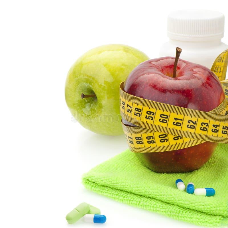 红色和绿色苹果、维生素和测量的磁带 免版税库存图片