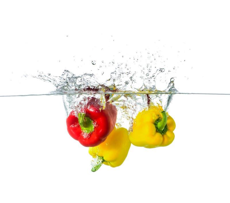 红色和黄色辣椒粉飞溅在水中 免版税库存照片