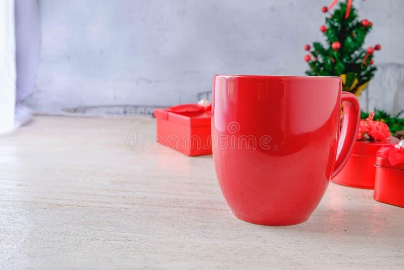 红色咖啡杯和红色礼物盒有圣诞树的在白色Bac 库存图片
