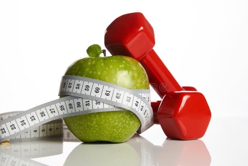 红色哑铃、新鲜的绿色苹果和测量的磁带 免版税库存照片