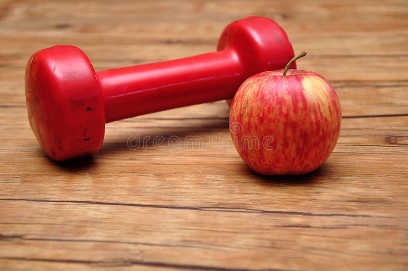 红色哑铃用苹果 库存照片