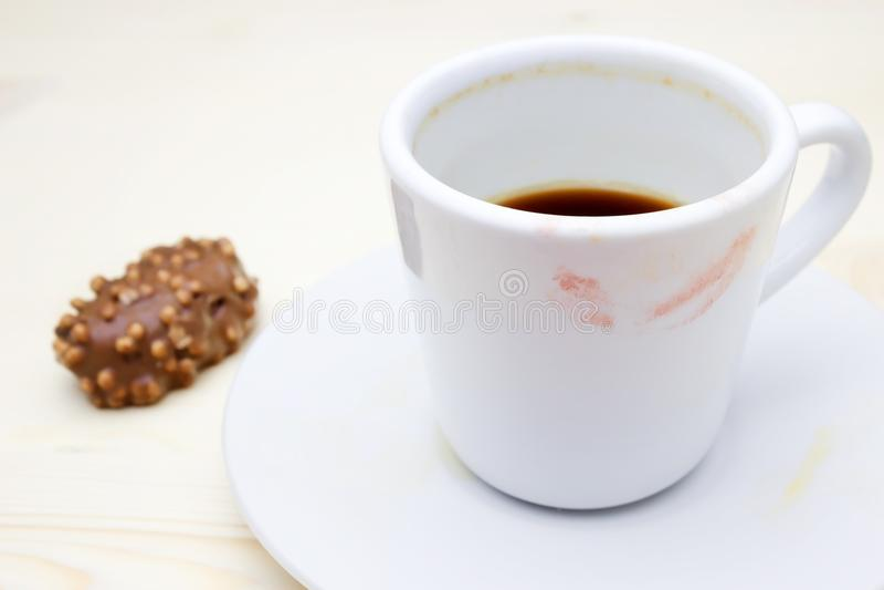 红色唇膏标记的照片在您的咖啡杯的 在板材和巧克力糖的肮脏的空的白色瓷杯子 Messthet 库存图片
