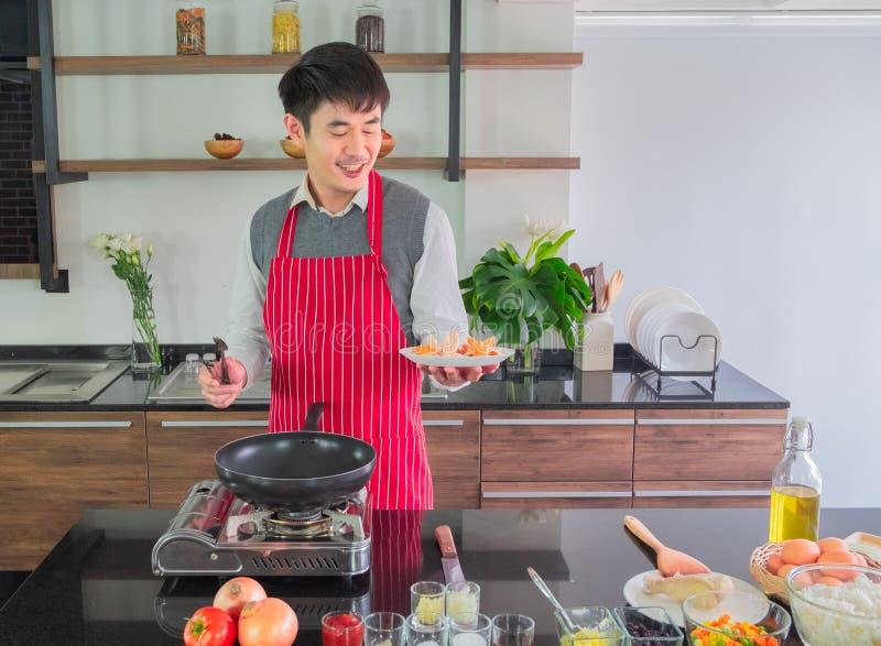 红色围裙的,与微笑的幸福亚裔年轻人 拿着油煎的香肠 免版税库存图片
