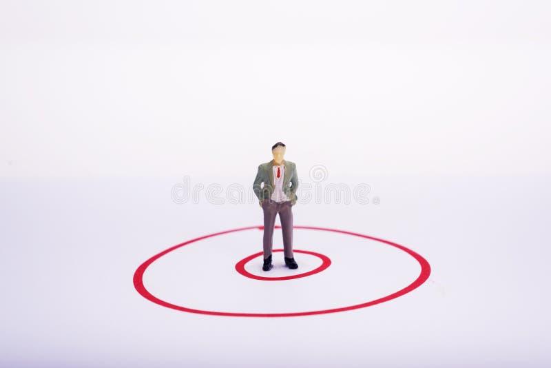 红色圆形图的微型人商人 库存照片
