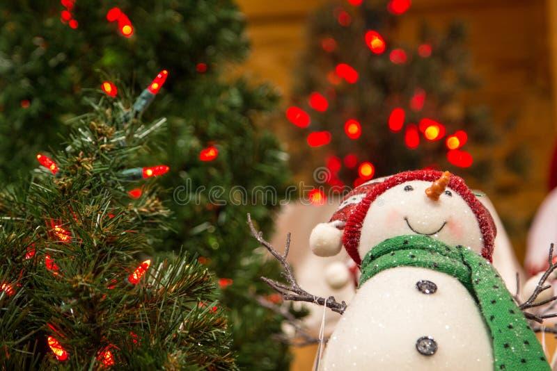 红色圣诞灯围拢的雪人装饰品 免版税图库摄影