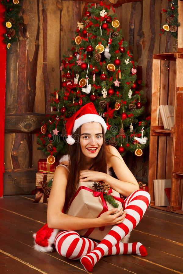 红色圣诞老人帽子和红色礼服的年轻愉快的妇女在新年t附近 免版税库存图片