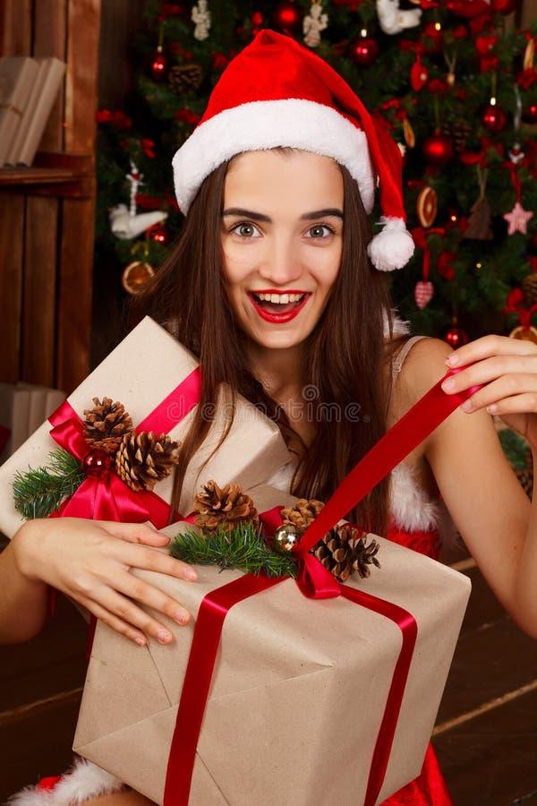 红色圣诞老人帽子和红色礼服的年轻愉快的妇女在新年t附近 免版税库存照片